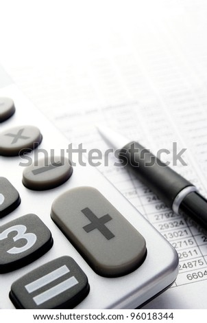 calculator, a pen and paper with numbers on the table - stock photo