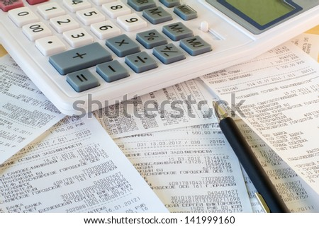 calculator, a receipt and a pen lying on the office table