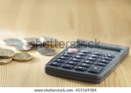 calculator and a stack of coins on a wooden table - stock photo