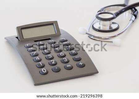 Calculator and a stethoscope on a white table - stock photo