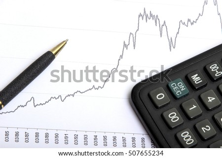 calculator and ballpoint pen on the background graphics of the stock exchange