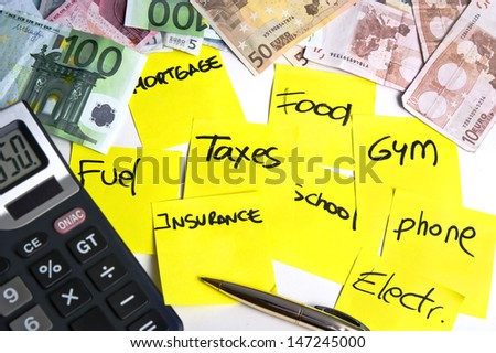 Calculator and banknotes on a table filled with yellow post it notes regarding cost of living: mortgage, taxes, fuel, food, school, phone, insurance, gym and electricity - stock photo
