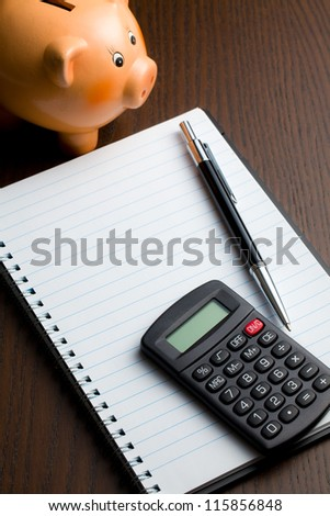calculator and blank notebook on table - stock photo
