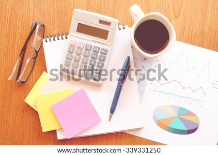 calculator and chart on the wooden table with vintage color style - stock photo