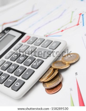 Calculator and coins on graphs. - stock photo