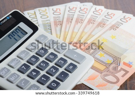 Calculator and euro banknotes on the table - stock photo