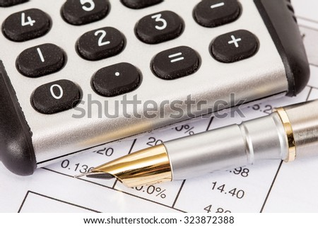Calculator and fountain pen on a business reports - stock photo