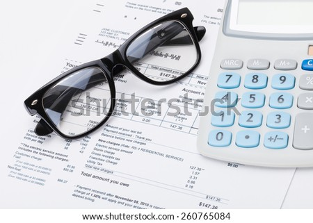 Calculator and glasses with utility bill under it - studio shot - stock photo