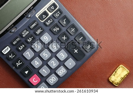 Calculator and gold bar put on the leather surface background represent the business and investment concept idea related. - stock photo
