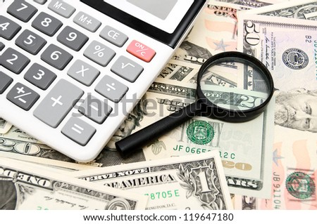 Calculator and magnifier on money. - stock photo