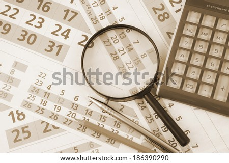 Calculator and magnifying glass on calendar