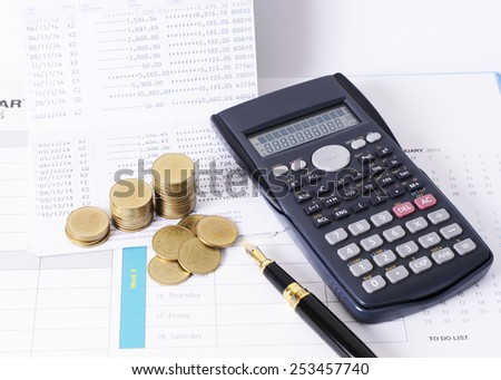Calculator and money coins stack with fountain pen for finance concept