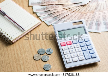 Calculator and money thai banknote (One thousand bath) with Thai baht coins (One bath)and white notebook paper and red pen on  wooden table. The concept of financial planning, savings. - stock photo