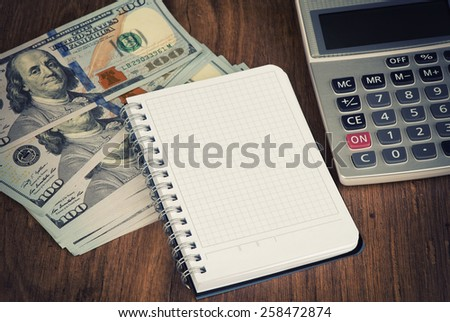 calculator and notepad lying on banknotes close up - stock photo