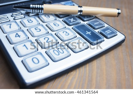 Calculator and pen in the wooden table