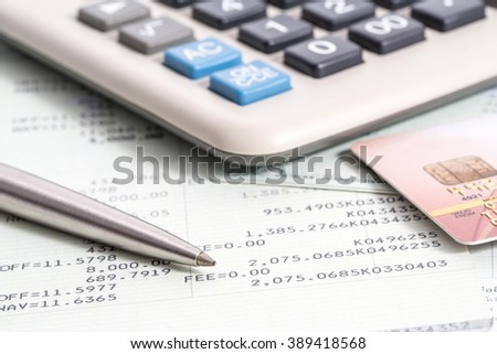 Calculator and pen on bank account passbook with dollar banknote, selective focus - stock photo