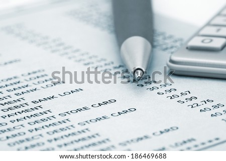 Calculator and Pen on Bank and credit card statements - stock photo