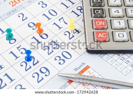 Calculator and pen on calendar  - stock photo