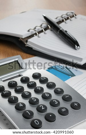 Calculator and pen on financial notebook in the diagram, as a background