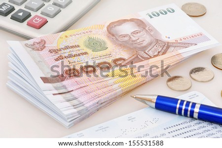 Calculator and pen on thai banknotes  - stock photo