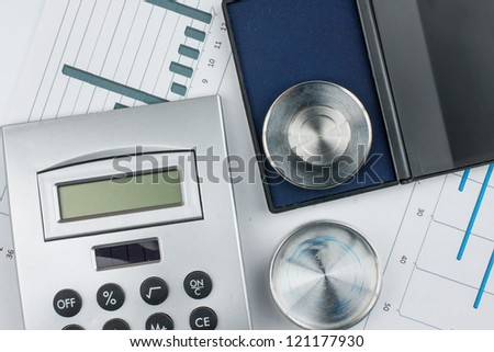 Calculator and print on a background of diagrams - stock photo