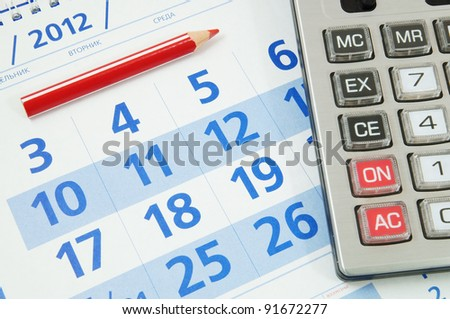 Calculator and red pencil on calendar - stock photo