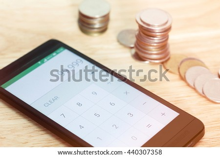 Calculator application with mobile phone and blurred currency coin background,Gradient filter effect,Saving money concept - stock photo