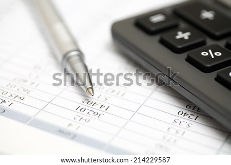 Calculator, ballpoint pen on financial statements. Closeup.