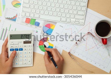Calculator, business diagrams, charts, and graphs on office desk - stock photo