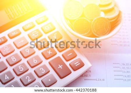 calculator,coin, Book bank statement on wooden floor - stock photo