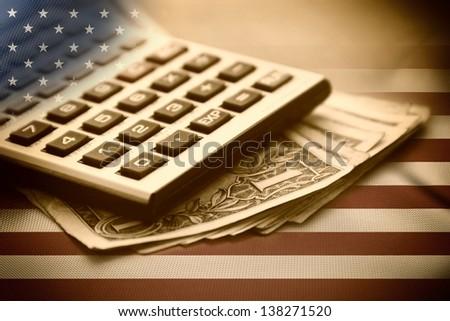 Calculator, dollars and USA flag. Sepia image. - stock photo