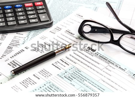Calculator, glasses and pen on tax form 1040.