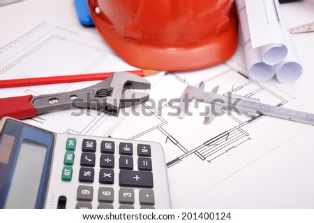 Calculator, helmet and drafting tools on architectural table