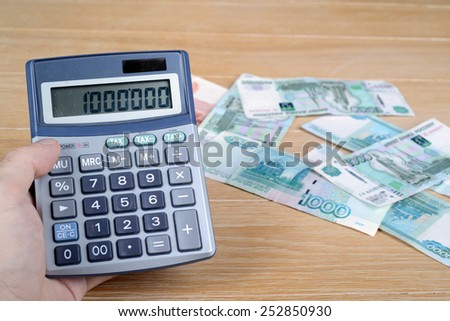 calculator in hand and rubles on a wooden table - stock photo