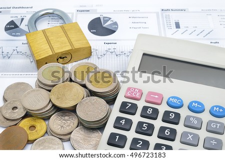 calculator, key and stack of coins on paper of financial graph