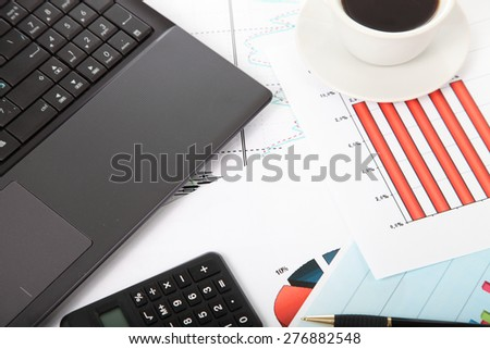 Calculator,laptop and cup of coffee on the financial documents on the table - stock photo