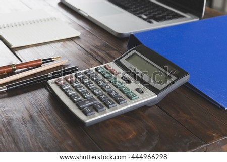 calculator, laptop computer, pen and notepad on wooden office desk