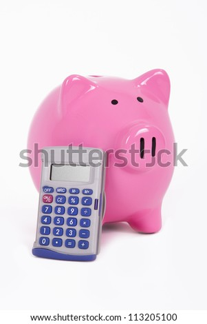 Calculator leans to pink piggy bank, isolated on white background. - stock photo