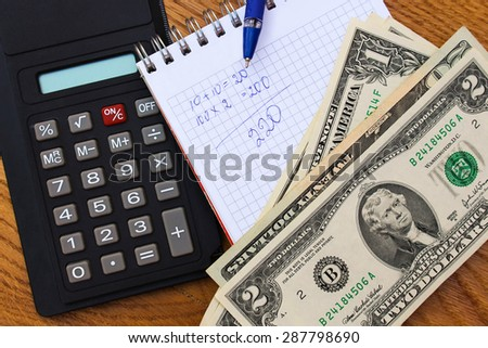 Calculator, money, notebook with calculations, pen on the table. - stock photo