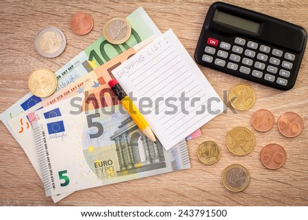 Calculator, money, pencil and empty lined paper to write a shopping list. - stock photo