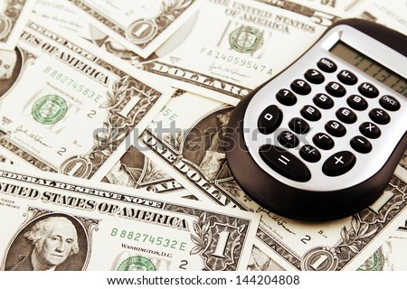 Calculator on American bank notes - stock photo