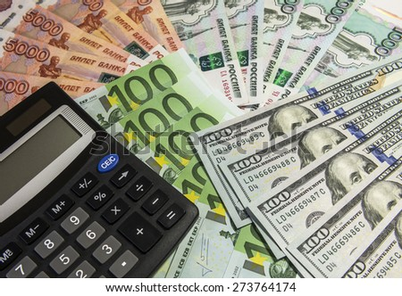 Calculator on background banknote 1000 and 5000 rubles, 100 euros and 100 dollars.