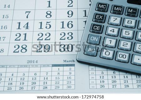Calculator on calendar background - stock photo