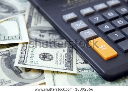 Calculator on cash money background of $100 banknotes