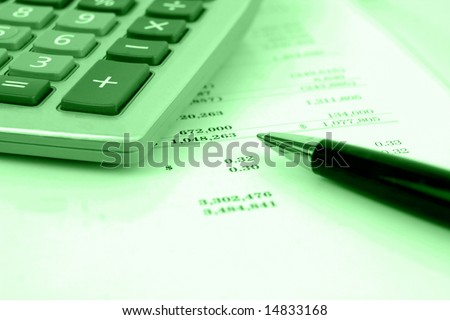 calculator on financial statement with green overlay and shallow Depth Of Field. - stock photo