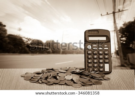 calculator on pile of coins with road and blue sky background - stock photo