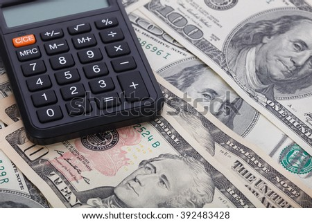 Calculator on the background of dollar banknotes - stock photo