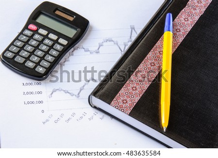 Calculator on the desk pen, calculations, chart, notebook, diary