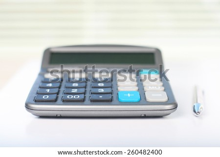 Calculator on white table in front of window - stock photo