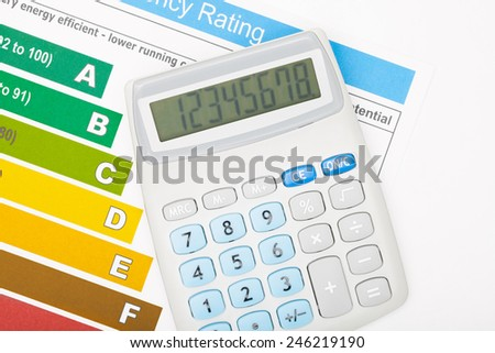 Calculator over energy efficiency chart - stock photo